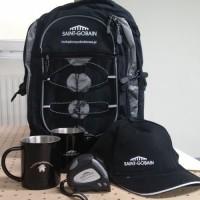 zestaw gadżetów reklamowyc: plecak, czapla z daszkiem, miarka oraz metalowy kubek z logo